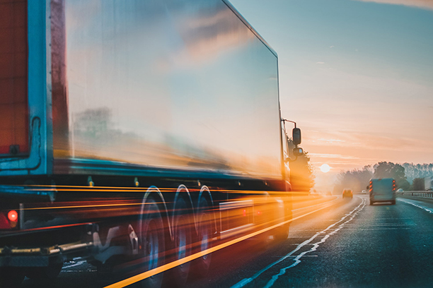 truck driving into sunset