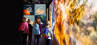 Panasonic Displays. Children looking at a display of the universe at a museum,