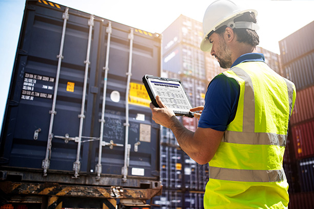 man with toughbook near shipping containers